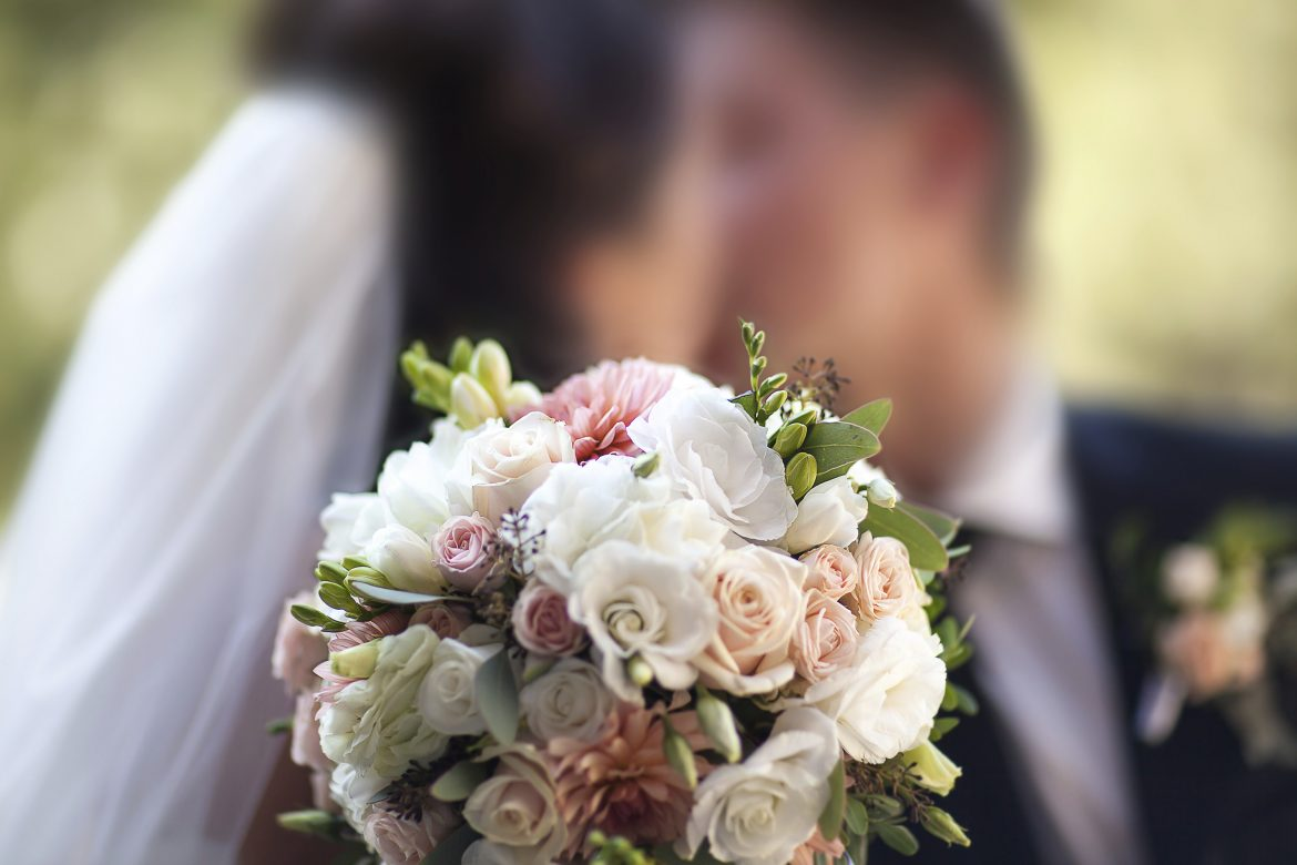 Wedding bouquet on a background of the bride and groom