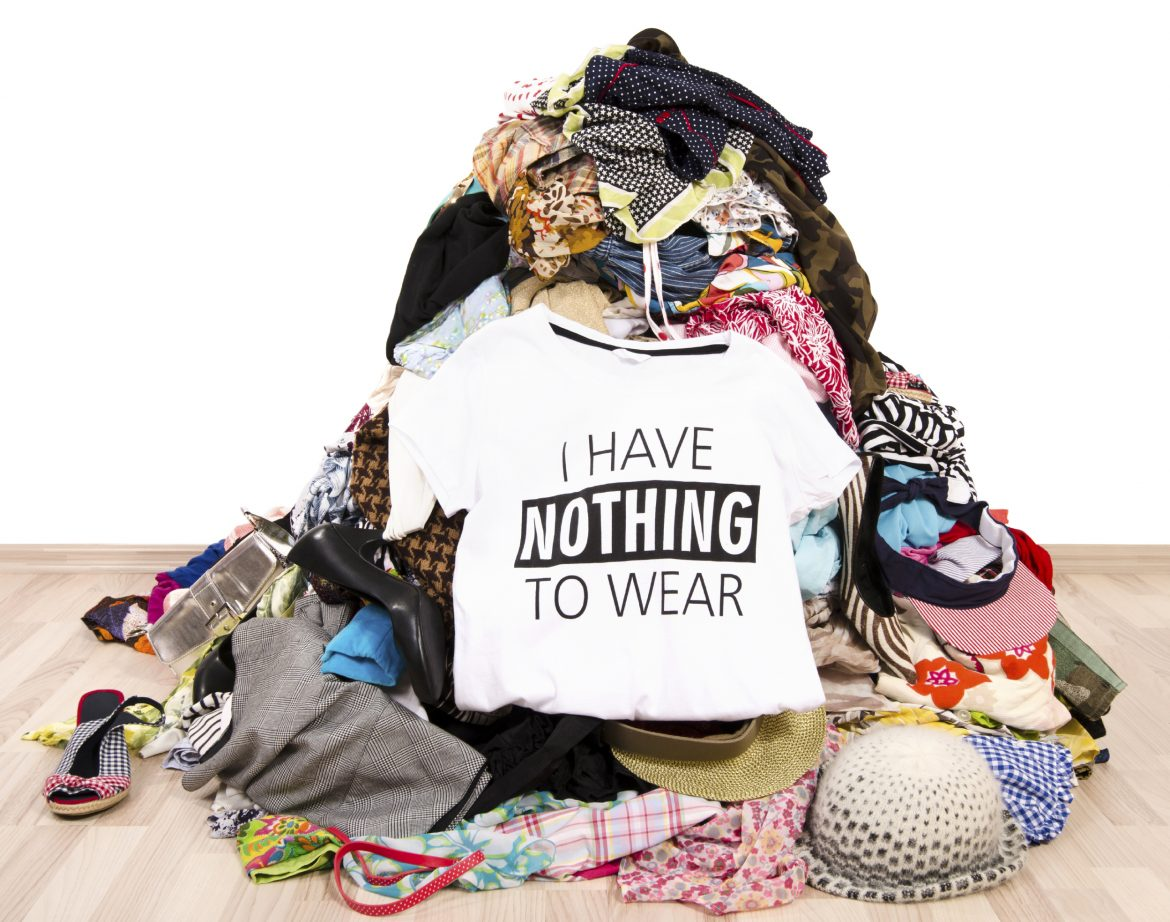 Close up on a untidy cluttered wardrobe with colorful clothes and accessories, many clothes and nothing to wear.