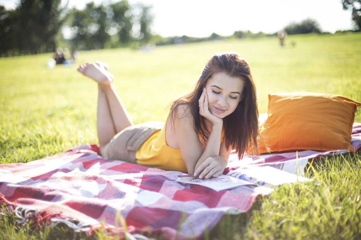 Young attractive woman reading a magazine on a meadow in a park
