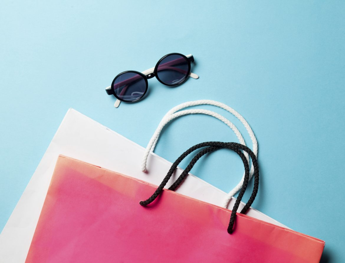 Shopping bags and sunglasses on blue background