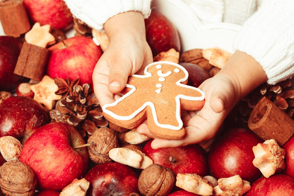 Child's hands hold a red apple and gingerman cookie
