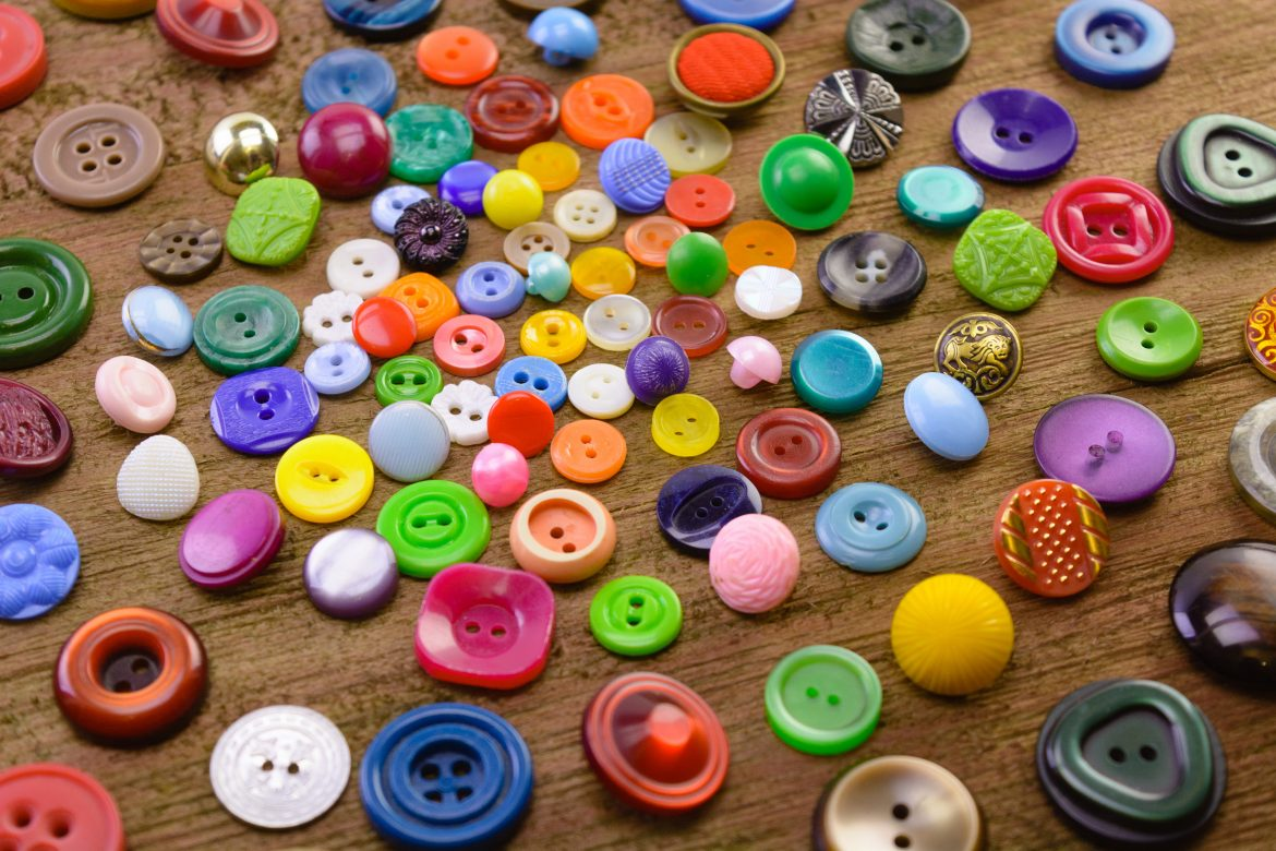 macro handful of multi-colored buttons for clothes on a wooden background