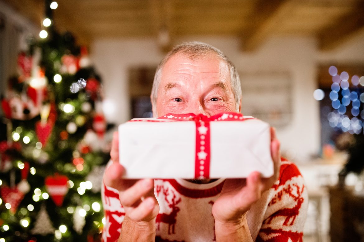 Senior man standing in front of illuminated Christmas tree inside his house holding a present, feeling pleased.